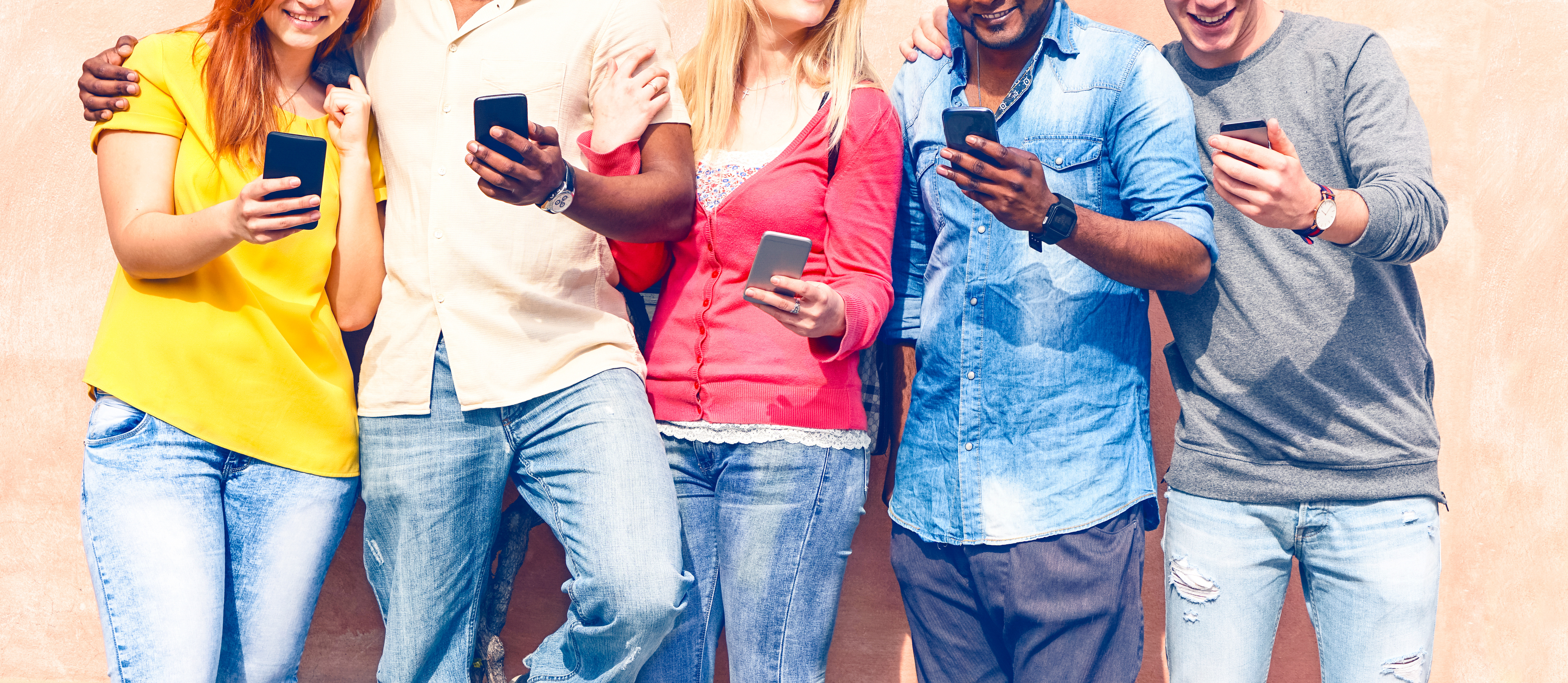 Teenagers texting mobile phone messages row on pink background - Multiracial friends holding smartphone outdoors - Modern communication concept - Image